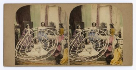 coloured-stereocard-entitled-putting-on-crinoline-depicting-a-woman-being-dressed-in-a-crinoline-published-by-the-london-stereoscopic-company-london-640x329